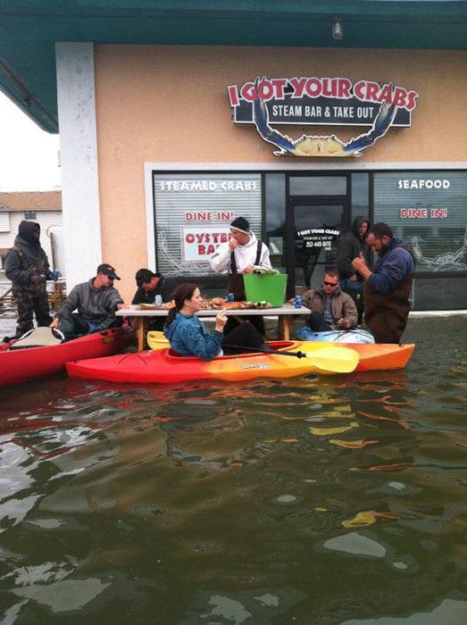personas en kayak comiendo en medio de una inundación