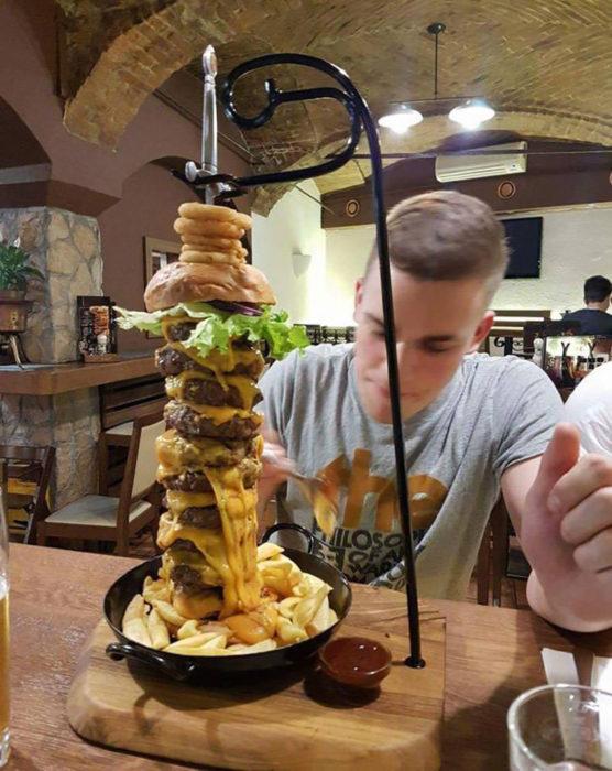 hombre comiendo una hamburguesa de múltiples pisos