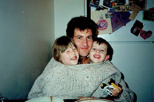 papá abrazando a sus hijos debajo de su suéter
