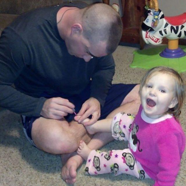papá haciendo la pedicura a su hijita