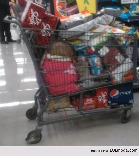 Niña en carrito de compras lleno