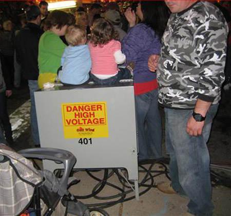 Niños sentados en caja que dice: riesgo alto voltaje