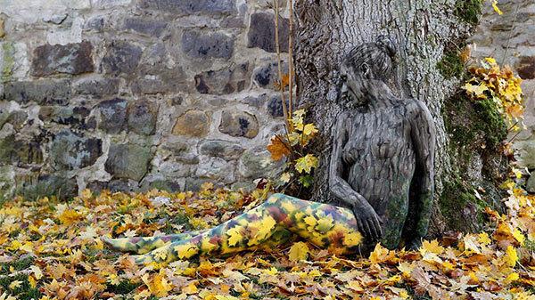 mujer pintada cual arbol y hojas