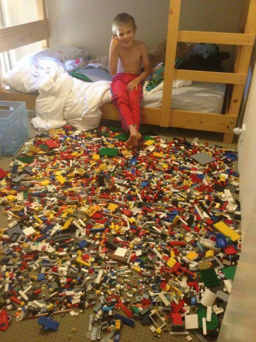 niño con una gran cantidad de legos regados por el suelo