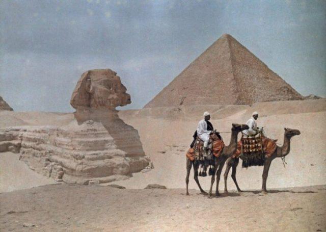 dos hombres montados en camellos cerca de las ruinas de Giza