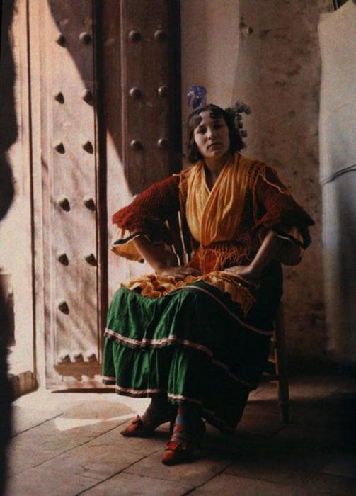 gitana posando en una silla utilizando su vestido tipico