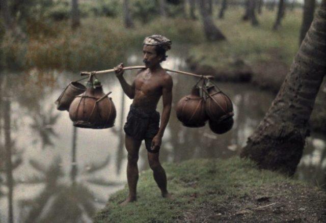 fotografía vieja de mozo cargando agua en calabazas