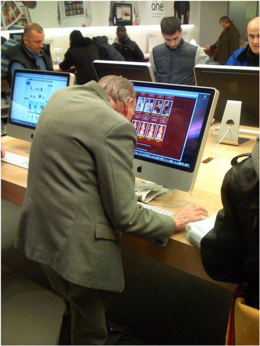 anciano en tienda de electronica visitando sitios de citas
