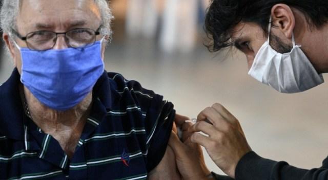 Un hombre mayor con barbijo recibe la vacuna.