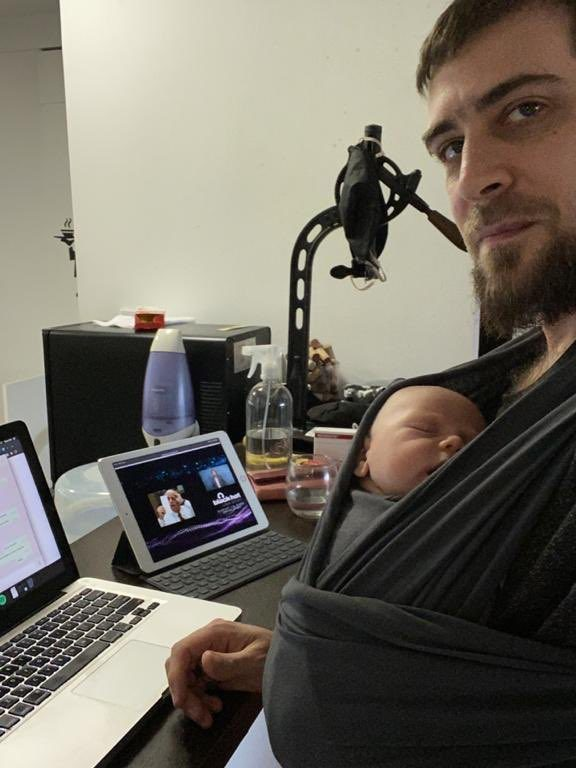 Un papá sentado frente a la compuadora, son su bebé en el fular.
