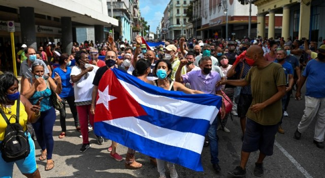 Ciudadanos cubanos en la calle, sostienen una bandera del país.