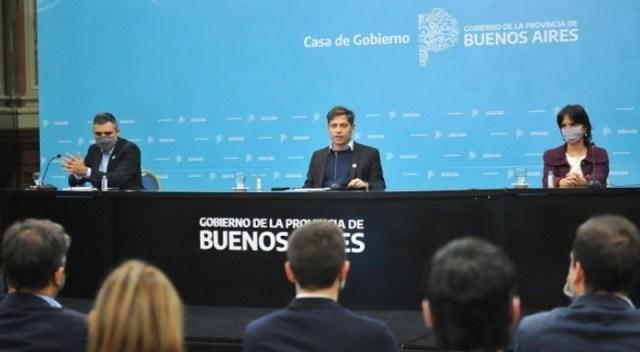 Tres personas dan una conferencia de prensa. En el medio, el gobernador Axel Kicillof.