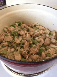 Diced onions, green bell peppers, and celery are cooked with bite-sized pieces of chicken in a cast iron pot.