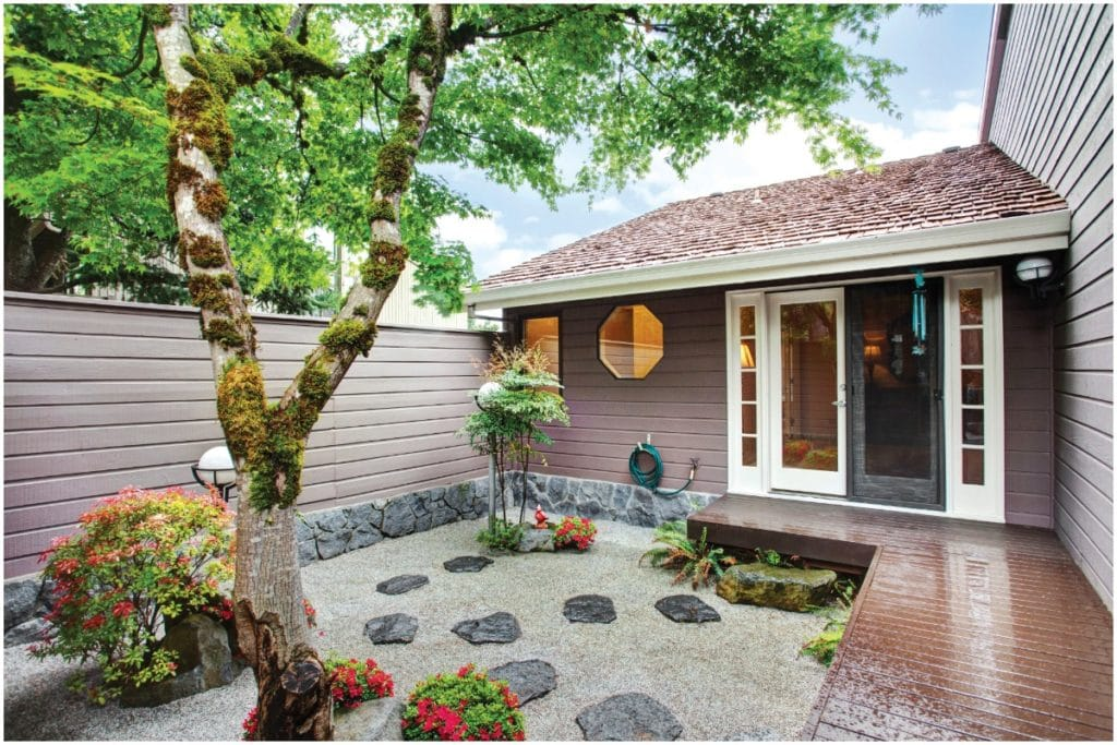 backyard porch with a rock garden and large tree