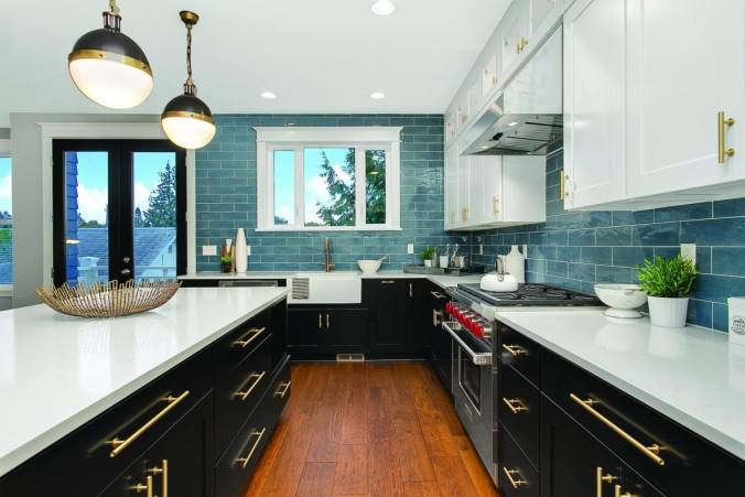 Kitchen with black cupboards, white countertop and blue tiled backsplash