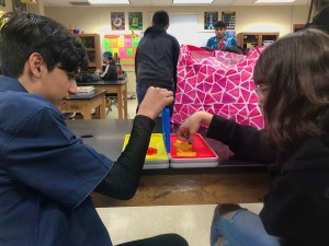Students use board games to pass time as their peers are benchmarking.