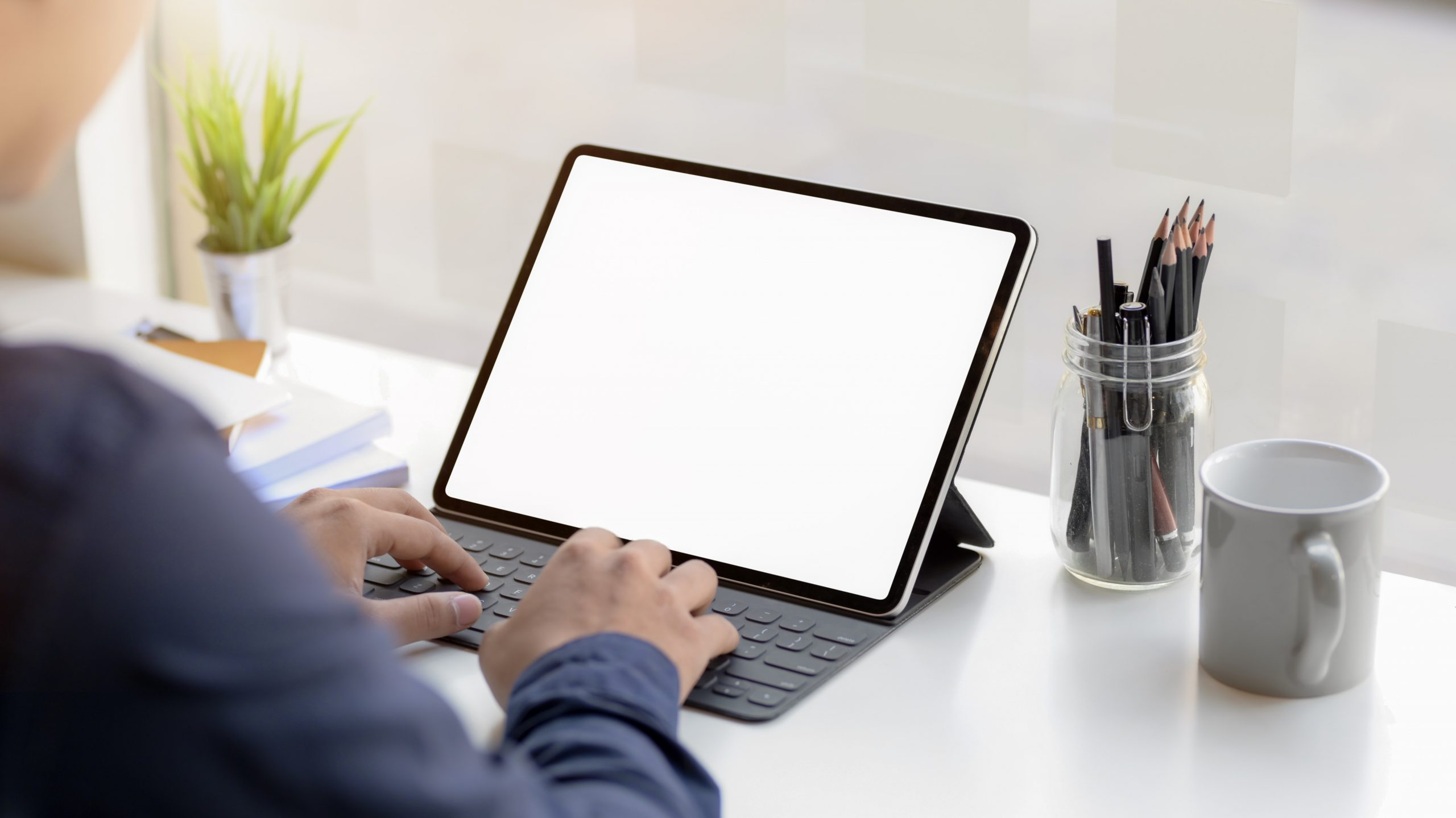 person-using-macbook-pro-on-white-table-3843359