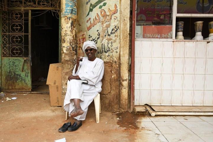 Menikmati minuman kopi di depan kios souq arabi