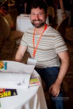 Bearded 2016 Sex Geek attendee looks up from a coloring book to smile for the camera