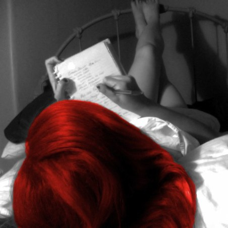 Woman lying on a bed with her legs up on the wrought iron headboard as she writes in a notebook. The top of her head is facing the camera. The photo is black and white and her hair is bright red.