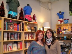 Two women - one brunette and one redhead- in front of bookshelves in a sex shop
