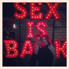 "Two women standing in front of a large red neon sign reading ""Sex is Back"""