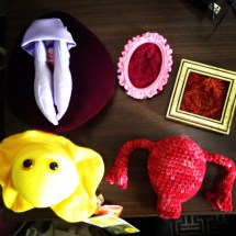 Table holding a vulva puppet, a crocheted uterus, 2 knit vulvas and a plush model of the herpes virus