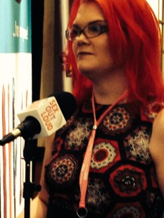 "JoEllen standing behind a microphone that reads ""Sex Out Loud"""