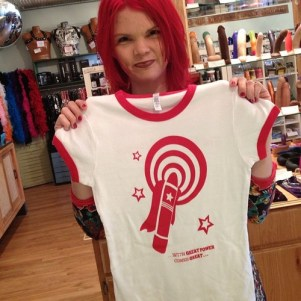 JoEllen holding a white t-shirt with red rings around the neck and sleeves and a red vibrator design
