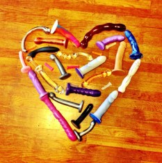 A large heart made out of sex toys on a wooden floor