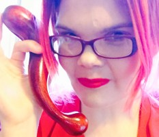 JoEllen in red glasses holding a curved wooden dildo