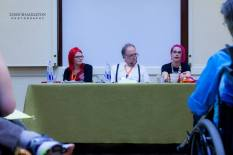A woman with red hair, a man with a goatee, and a woman with pink hair sitting behind a table for a panel discussion