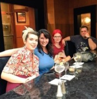Three women, one in a kerchief, one redhead, and one brunette and a man at a bar.