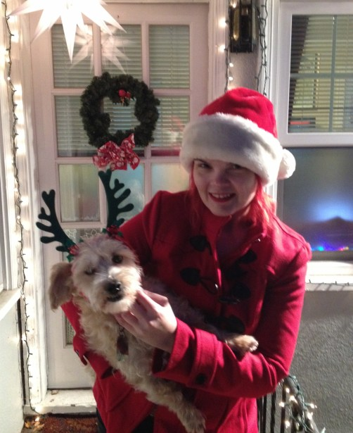 Red haired woman (JoEllen) in Santa hat holding small beige dog wearing antlers