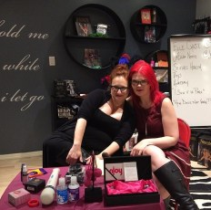Two women, both redheads, pose on a small stage in a sex shop