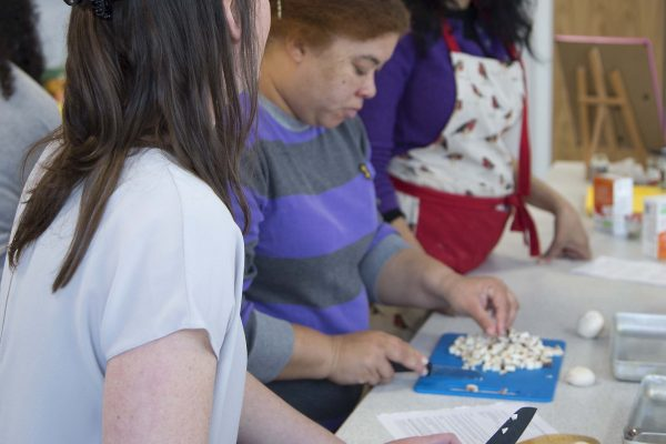 A photograph of two women chopping mushrooms as part of a cooking class at The Red Hen Project