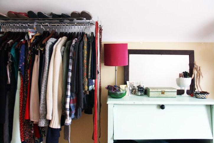 Clothes rack next to blue dresser.