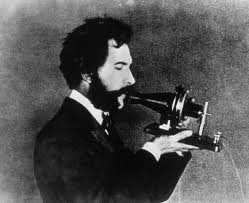 Alexander Graham Bell with his first telephone