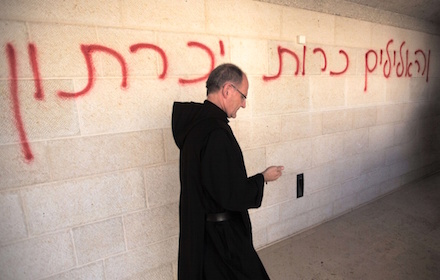 "A priest walks past Hebrew graffiti reading ""idols will be killed"" at the burned Tabghe Church in the Galilee."