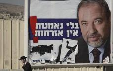 "An ultra-Orthodox Jewish man passes an election campaign poster for the leader of Israel's right-wing Yisrael Beiteinu Party, Avigdor Lieberman, in Jerusalem, Thursday Feb. 5, 2009. General elections in Israel are scheduled for Feb. 10, 2009, and pre-election polls show Likud Party leader Benjamin Netanyahu with a lead over Foreign Minister and Kadima Party leader Tzipi Livni. The campaign slogan on the poster reads ""Without loyalty, there is no citizenship."" (AP Photo/Peter Dejong)"