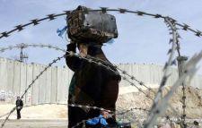 Palestinian woman walks next to the Apartheid Wall