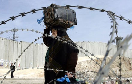Palestinian woman walks next to the Apartheid Wall