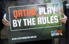 Person holding placard saying Qatar Play Fair