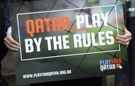 Person holding placard saying Qatar Play Fair