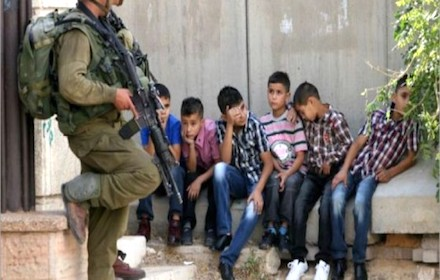 Israeli solder pointing gun at children