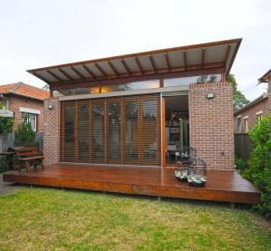 The addition appears as a pavilion in the rear garden. Glazed doors looking out over the rear deck and garden, and highlight windows allowing the roof to float over its brick walls.
