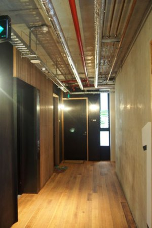 Lift foyers, natural light & ventilation from the light well. Warm recycled timber finish contrasted against concrete finishes.