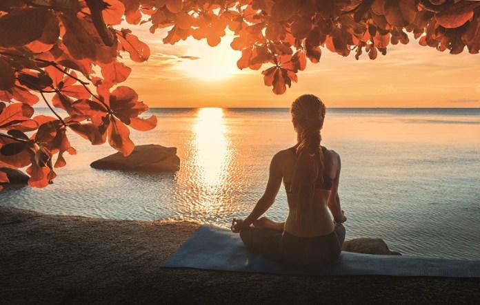 frau-sitzt-am-meer-und-meditiert-im-sonnenuntergang