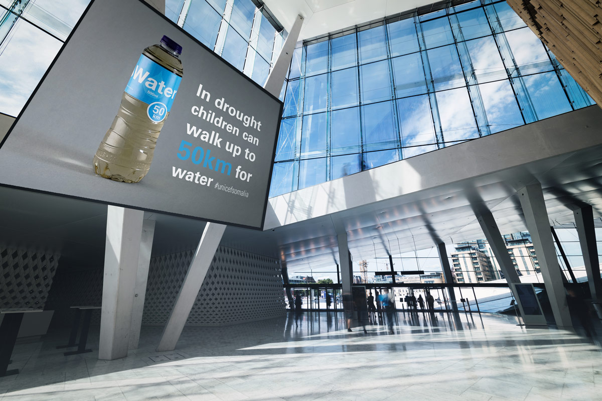 Billboard with a picture of bottled water describing how far children have to walk for clean water