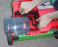 The battery fits snugly onto the top of the reel mower body.